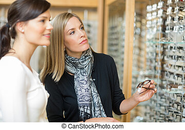 Woman With Salesgirl Selecting Eyeglasses - Beautiful woman...
