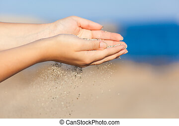 Woman with sand falling through her hands