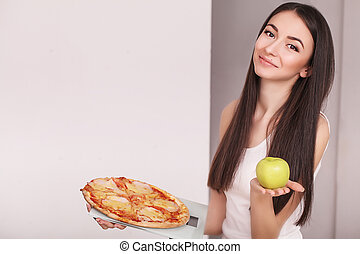 Woman with scales choosing craving slice of pizza instead of green apple