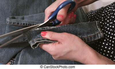 Woman with scissors cutting bottom of the Jeans