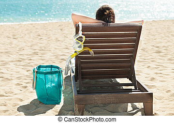 Woman with scuba mask relaxing on deck chair at beach resort