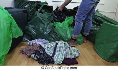 Woman with second hand clothes near plastic bags