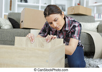woman with self assembly furniture in kitchen