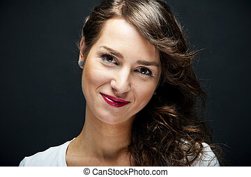 Woman with sensual smile on black background
