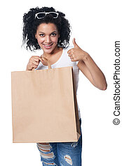 Woman with shopping bag gesturing thumb up
