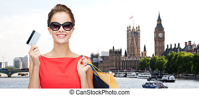woman with shopping bag in and credit card london