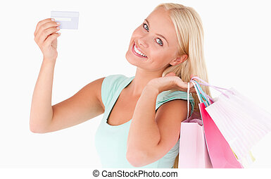 Woman with shopping bags and a credit card in a studio