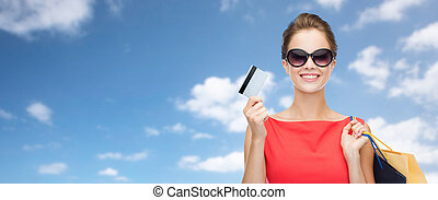 woman with shopping bags and credit card over sky