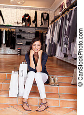Woman With Shopping Bags And Shoes Sitting On Boutique Steps