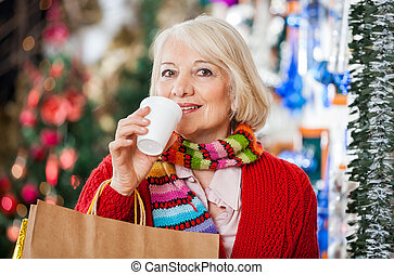 Woman With Shopping Bags Drinking Coffee At Christmas Store...
