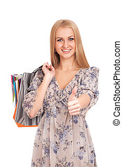 Woman with shopping bags gesturing thumbs up