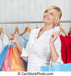 Woman With Shopping Bags Holding Blank Credit Card In Shop