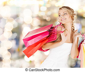 woman with shopping bags in dress - retail and sale concept...