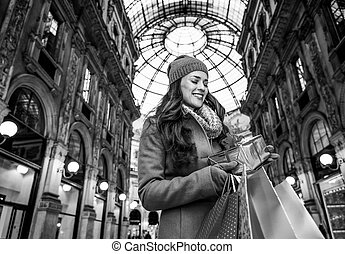woman with shopping bags in Milan looking on Christmas gift