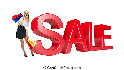 Woman with shopping bags next to sale sign