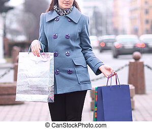 woman with shopping bags on the background of the city