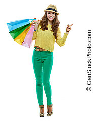 Woman with shopping bags pointing aside on white background...