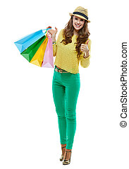 Woman with shopping bags showing thumbs up on white background