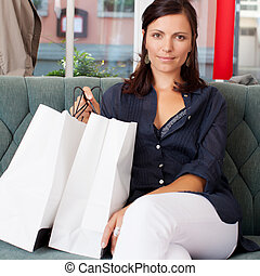 Woman With Shopping Bags Sitting On Sofa At Clothing Store
