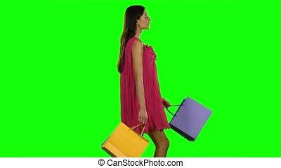 Woman with shopping bags walking. Green screen