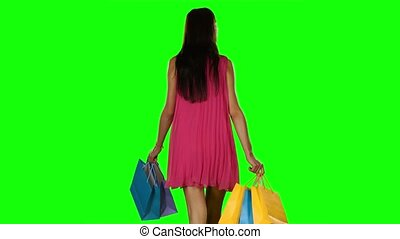 Woman with shopping bags walking in the mall. Green screen
