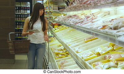 Woman with shopping cart buying refrigerated groceries at supermarket and using tablet pc to check shopping list. Girl coming up to the fridge in shop, taking product and putting it into the basket