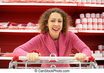 woman with shopping cart in supermarket