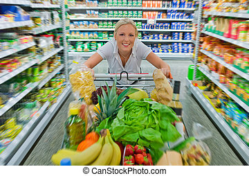 woman with shopping cart in the supermarket - a woman in the...