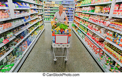 woman with shopping cart in the supermarket - a woman when ...