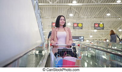 Woman with shopping cart on escalator in mall