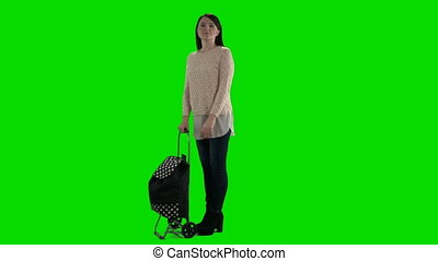 Woman with shopping rolling bag cart against a green screen
