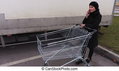 Woman with shopping trolley talking on smartphone