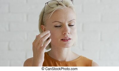 Woman with short hair applying cream - Pretty young female...