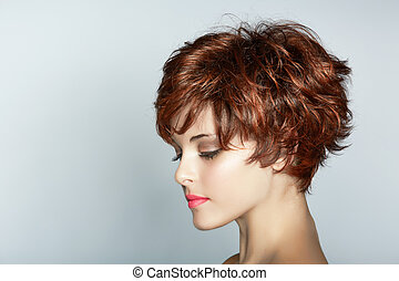 beautiful young woman with short brown haircut wears pink lipstick on studio background with copy space.