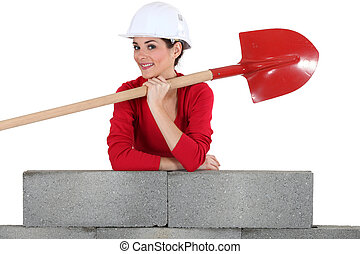 Woman with shovel leaning against a wall