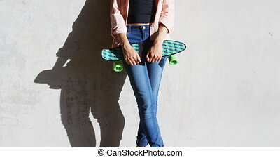 Woman with skate board leaning against wall under flyover 4k...