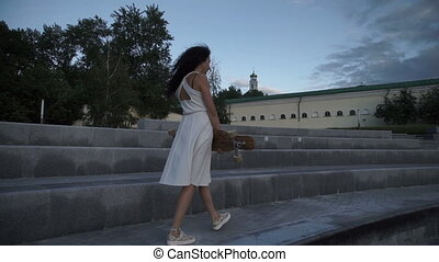 Woman with skate in hands walking