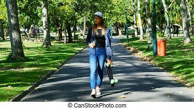 Woman with skateboard walking on street near park 4k -...