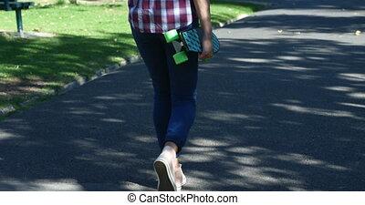 Woman with skateboard walking on street near park 4k - Rear...