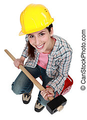 Woman with sledge-hammer sitting on tool box