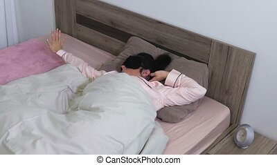 Woman with sleeping mask stretching in bed at home