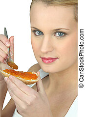 Woman with slice of bread with jam