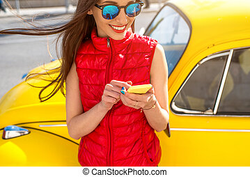 Woman using smart phone near her yellow old fashioned car on the street