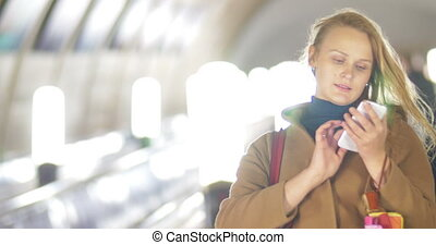 Woman with smart phone on subway escalator