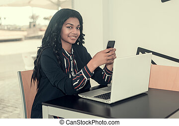 woman with smart phone working on the computer