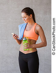 woman with smartphone and bottle of water in gym