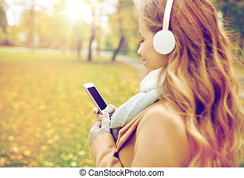 woman with smartphone and earphones in autumn park - season,...