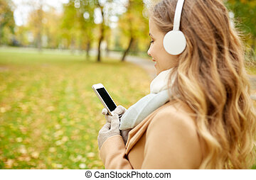 woman with smartphone and earphones in autumn park - season...