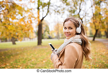woman with smartphone and earphones in autumn park