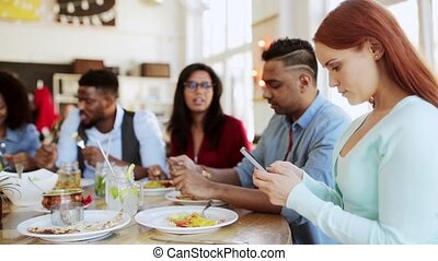 woman with smartphone and friends at restaurant